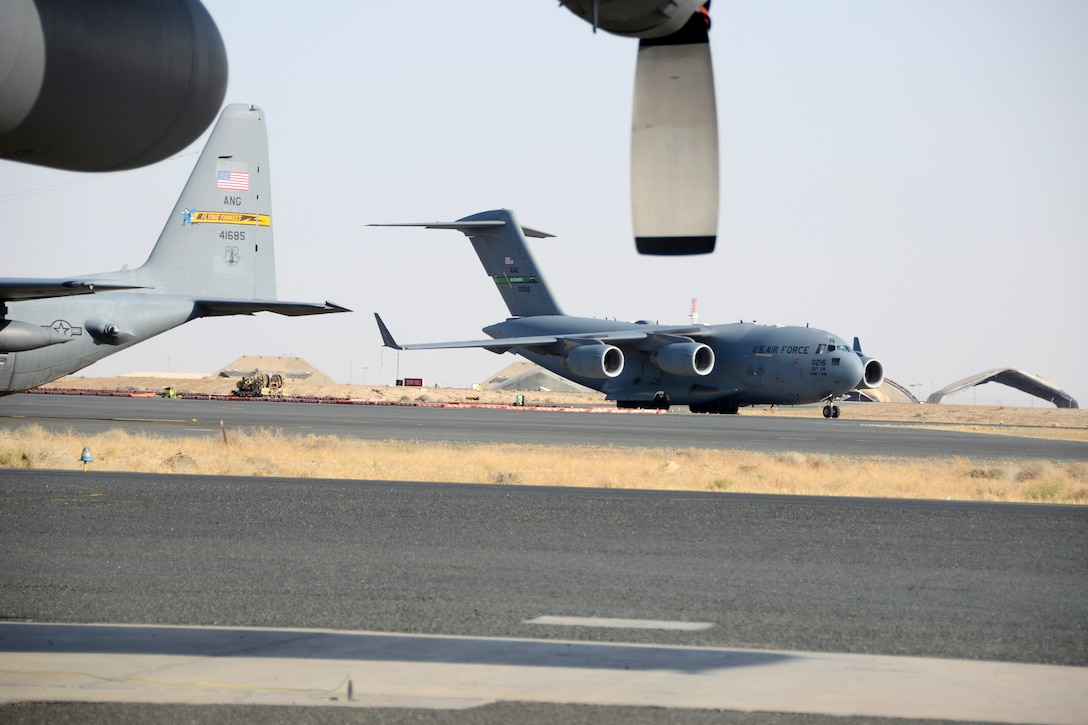 A C-17 Globe Master III taxis past a C-130 Hercules at Ali Al Salem Air Base, Kuwait, July 3, 2019. The units are currently deployed here providing tactical airlift to the Central Command Area of Responsibility. (U.S. Air National Guard photo by Capt. Stephen Hudson/Released)