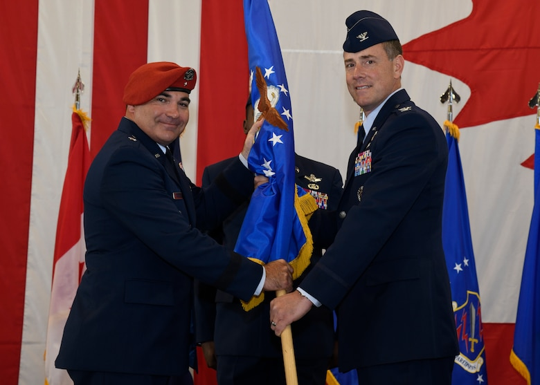 Col. Thomas G. Falzarano (right) receives the 21st Space Wing guidon from Brig. Gen. Matthew W. Davidson (left), 14th Air Force vice commander, as he assumes command during the wing's change of command ceremony July 10, 2019, at Peterson Air Force Base, Colorado. He oversees the Air Force's fifth largest wing which consists of a work force of about 4,300 space professionals worldwide. (U.S. Air Force photo by Craig Denton)
