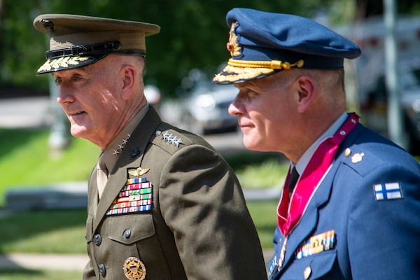 Two military commanders walk together during a ceremony.