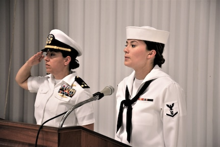 IMAGE: (Left to right) Chief Warrant Officer Josephine Leon, master of ceremony, renders a salute prior to Musician 3rd Class Amanda Huddleston, Fleet Forces Band, singing the national anthem. More than 200 Sailors and guests attended a traditional change of command ceremony at Naval Air Station (NAS) Oceana's Center for Naval Aviation Technical Training Unit's ceremonial hangar aboard NAS Oceana June 27 where Cmdr. Andrew Hoffman was relieved of command by Cmdr. Joseph Oravec. Oravec became the 28th commanding officer, Naval Surface Warfare Center Dahlgren Division, Dam Neck Activity.