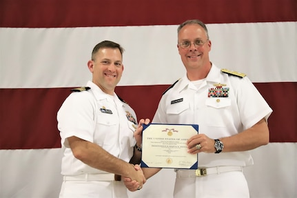 IMAGE: (Left to right) Cmdr. Andrew Hoffman receives the Meritorious Service Medal (Gold Star in lieu of the Second Award) from Rear Adm. Eric Ver Hage, Commander NAVSEA Warfare Centers, for his achievements as Naval Surface Warfare Center Dahlgren Division, Dam Neck Activity's commanding officer. More than 200 Sailors and guests attended a traditional Change of Command ceremony at Naval Air Station (NAS) Oceana's Center for Naval Aviation Technical Training Unit's ceremonial hangar aboard NAS Oceana June 27 where Hoffman was relieved of command by Cmdr. Joseph Oravec. Oravec became the command's 28th commanding officer.