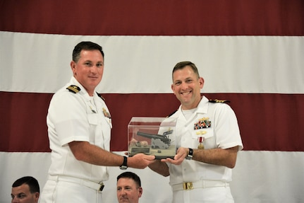 "IMAGE: (Left to right) Cmdr. Casey Plew, Commanding Officer, Naval Surface Warfare Center Dahlgren Division (NSWCDD), presents Cmdr. Andrew Hoffman with a farewell ""token"" for his 40 months as NSWCDD Dam Neck Activity's commanding officer. More than 200 Sailors and guests attended a traditional Change of Command ceremony at Naval Air Station (NAS) Oceana's Center for Naval Aviation Technical Training Unit's ceremonial hangar aboard NAS Oceana June 27 where Hoffman was relieved of command by Cmdr. Joseph Oravec. Oravec became the command's 28th commanding officer."