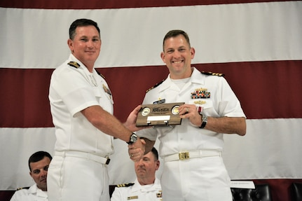 IMAGE: (Left to right) Cmdr. Casey Plew, Commanding Officer, Naval Surface Warfare Center Dahlgren Division (NSWCDD), presents Cmdr. Andrew Hoffman with a farewell plaque for his three plus years as NSWCDD Dam Neck Activity's commanding officer. More than 200 Sailors and guests attended a traditional Change of Command ceremony at Naval Air Station (NAS) Oceana's Center for Naval Aviation Technical Training Unit's ceremonial hangar aboard NAS Oceana June 27 where Hoffman was relieved of command by Cmdr. Joseph Oravec. Oravec became the command's 28th commanding officer.
