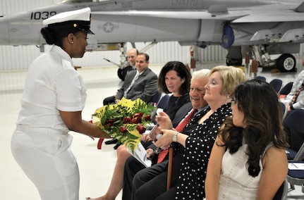 IMAGE: (Left) Chief Logistics Specialist Kisha Vilabrera presents flowers to Cmdr. Andrew Hoffman's mother honoring her role on the home front during a traditional Change of Command ceremony at Naval Air Station (NAS) Oceana's Center for Naval Aviation Technical Training Unit's ceremonial hangar aboard NAS Oceana June 27. Hoffman was relieved by Cmdr. Joseph Oravec as Naval Surface Warfare Center Dahlgren Division, Dam Neck Activity's commanding officer. Oravec becomes the 28th commanding officer for the Virginia Beach, Virginia command.