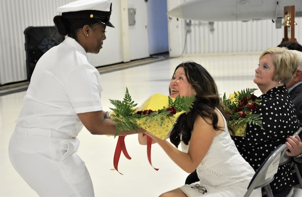 IMAGE: : (Left) Chief Logistics Specialist Kisha Vilabrera presents flowers to Cmdr. Andrew Hoffman's wife honoring her role on the home front during a traditional Change of Command ceremony at Naval Air Station (NAS) Oceana's Center for Naval Aviation Technical Training Unit's ceremonial hangar aboard NAS Oceana June 27. Hoffman was relieved by Cmdr. Joseph Oravec as Naval Surface Warfare Center Dahlgren Division, Dam Neck Activity's commanding officer. Oravec becomes the 28th commanding officer for the Virginia Beach, Virginia command.