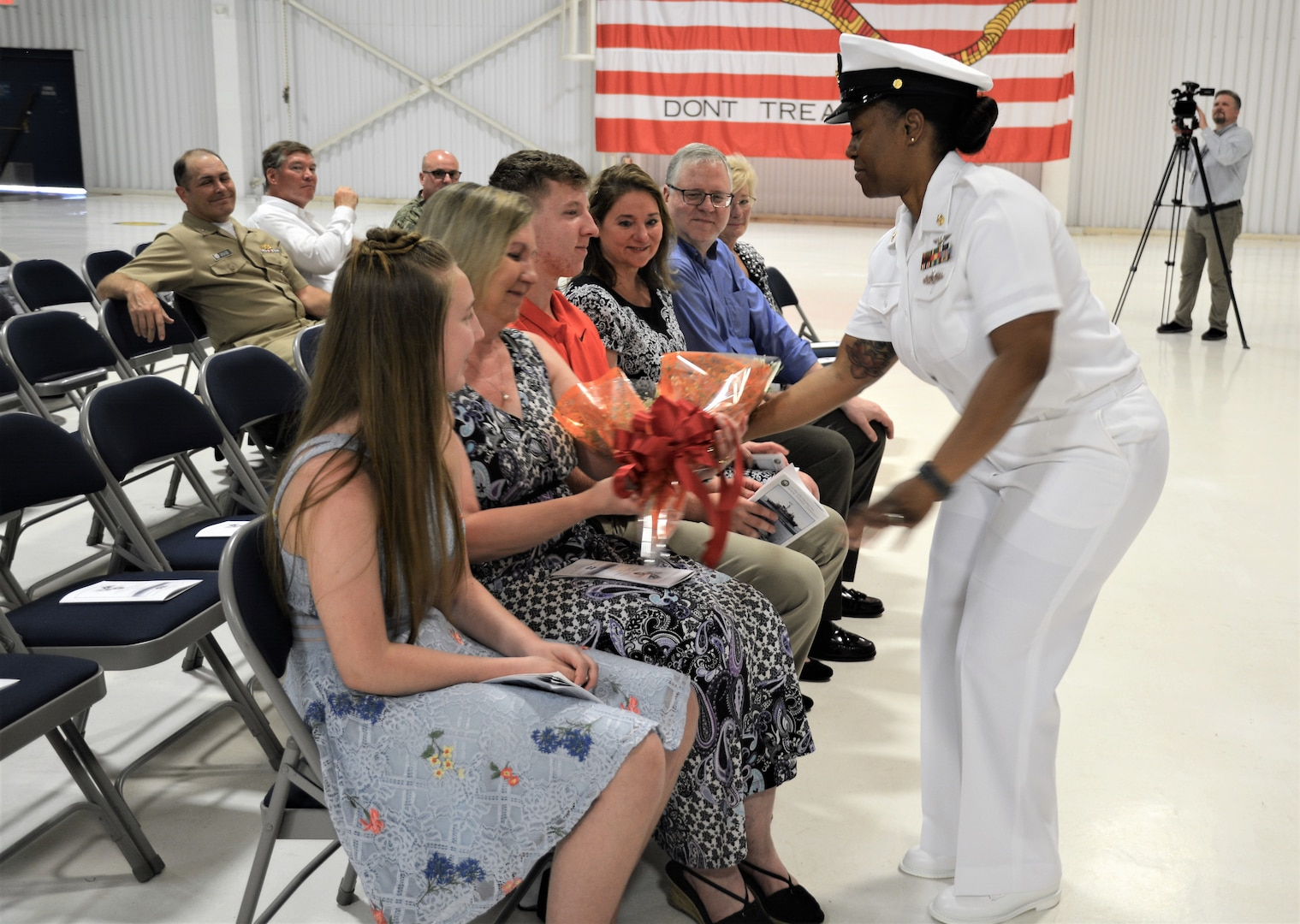 IMAGE: (Center) Chief Logistics Specialist Kisha Vilabrera presents flowers to Cmdr. Joseph Oravec's wife honoring her role on the home front during a traditional Change of Command ceremony at Naval Air Station (NAS) Oceana's Center for Naval Aviation Technical Training Unit's ceremonial hangar aboard NAS Oceana June 27. Oravec relieved Cmdr. Andrew Hoffman and became Naval Surface Warfare Center Dahlgren Division, Dam Neck Activity's 28th commanding officer.