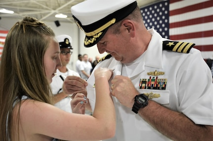 IMAGE: (Left to right) Cmdr. Joseph Oravec's daughter pins the Commanding Officer Ashore pin to her father's shirt following Naval Surface Warfare Center Dahlgren Division, Dam Neck Activity's change of command. More than 200 Sailors and guests attended a traditional ceremony at Naval Air Station (NAS) Oceana's Center for Naval Aviation Technical Training Unit's ceremonial hangar aboard NAS Oceana June 27 where Cmdr. Andrew Hoffman was relieved of command by Oravec. Oravec became the command's 28th commanding officer.