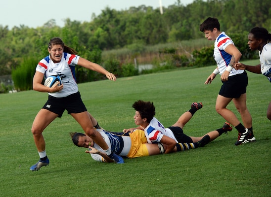 WILMINGTON, N.C. (June 6, 2019) -- Marine Capt. Kate Herren carries the ball down the pitch in the face of intense Navy defense during the Marine Corps-Navy rugby match on day two of the inaugural Armed Forces Women's Rugby Championship held in Wilmington, N.C. July 5-7, 2019. This historic event features the best female rugby players from the Army, Marine Corps, Navy, Air Force, and Coast Guard, who will compete for the title of the first ever Women's Rugby Champs (U.S. Dept. of Defense photo by Chief Mass Communication Specialist Patrick Gordon/RELEASED)