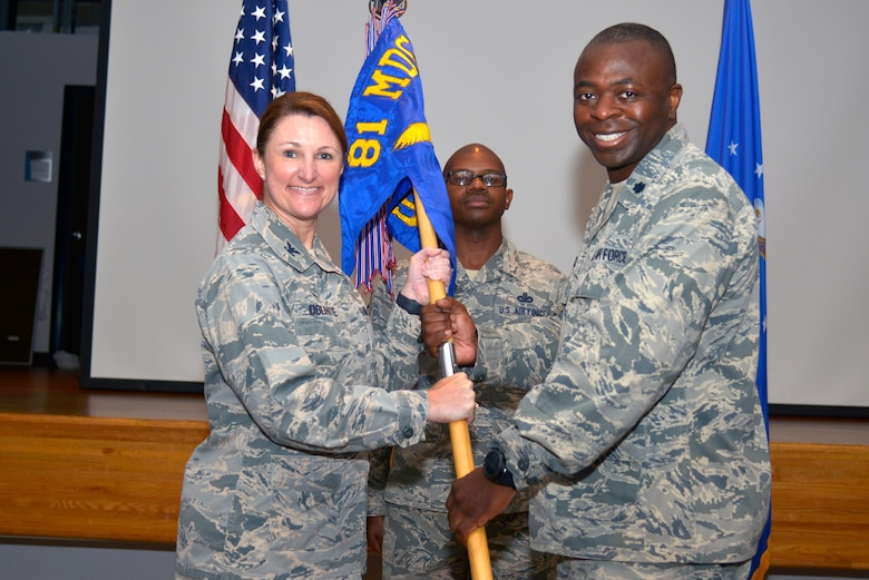 U.S. Air Force Col. Beatrice Dolihite, 81st Medical Group service commander, passes the 81st Surgical Operations Squadron guidon to Lt. Col. Norris Jackson, incoming 81st MSGS commander, during the 81st MSGS change of command ceremony inside the Don Wylie Auditorium at Keesler Air Force Base, Mississippi, July 9, 2019. The passing of the guidon is a ceremonial symbol of exchanging command from one commander to another. Jackson assumed command from Col. Ryan Mihata, outgoing 81st MSGS commander. (U.S. Air Force photo by Airman Seth Haddix)