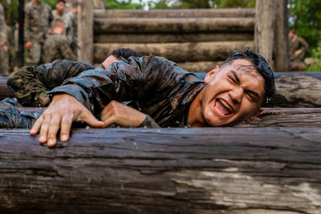 A Marine climbs over an obstacle.