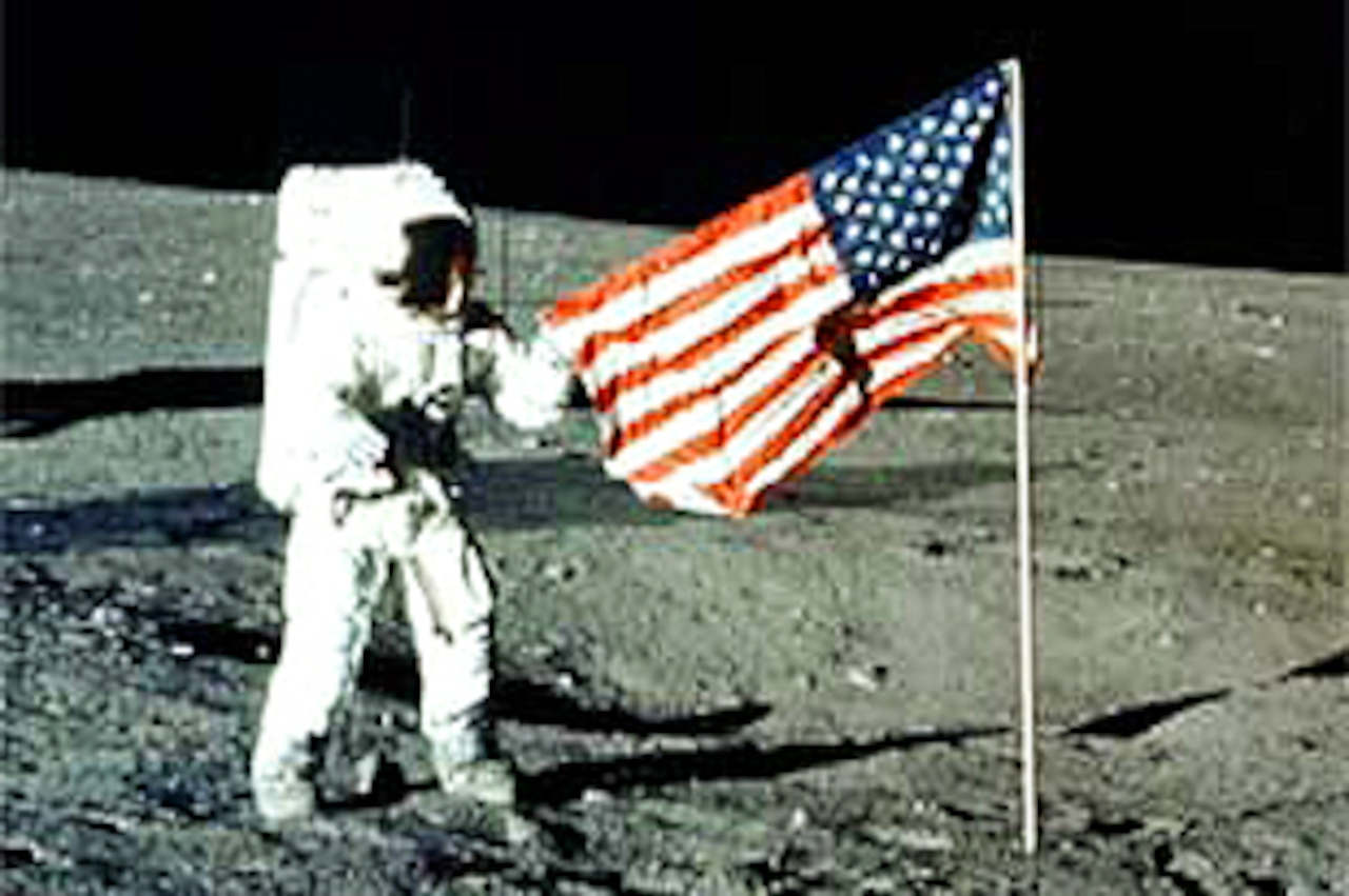Neil Armstrong stands on the moon next to an American flag.