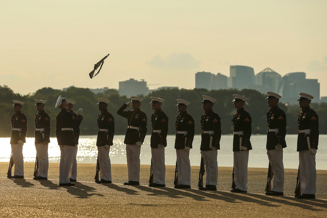 Marines stand in a line outside as one tosses a rifle in the air.
