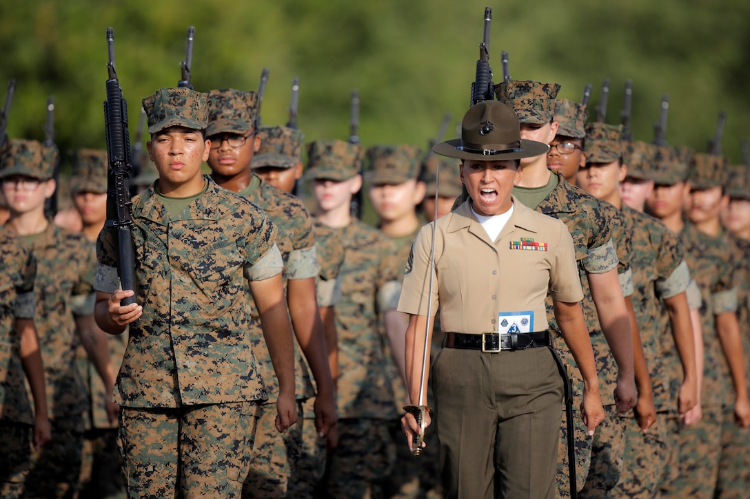 A Marine shouts as a group of Marines stand in lines holding weapons behind her.