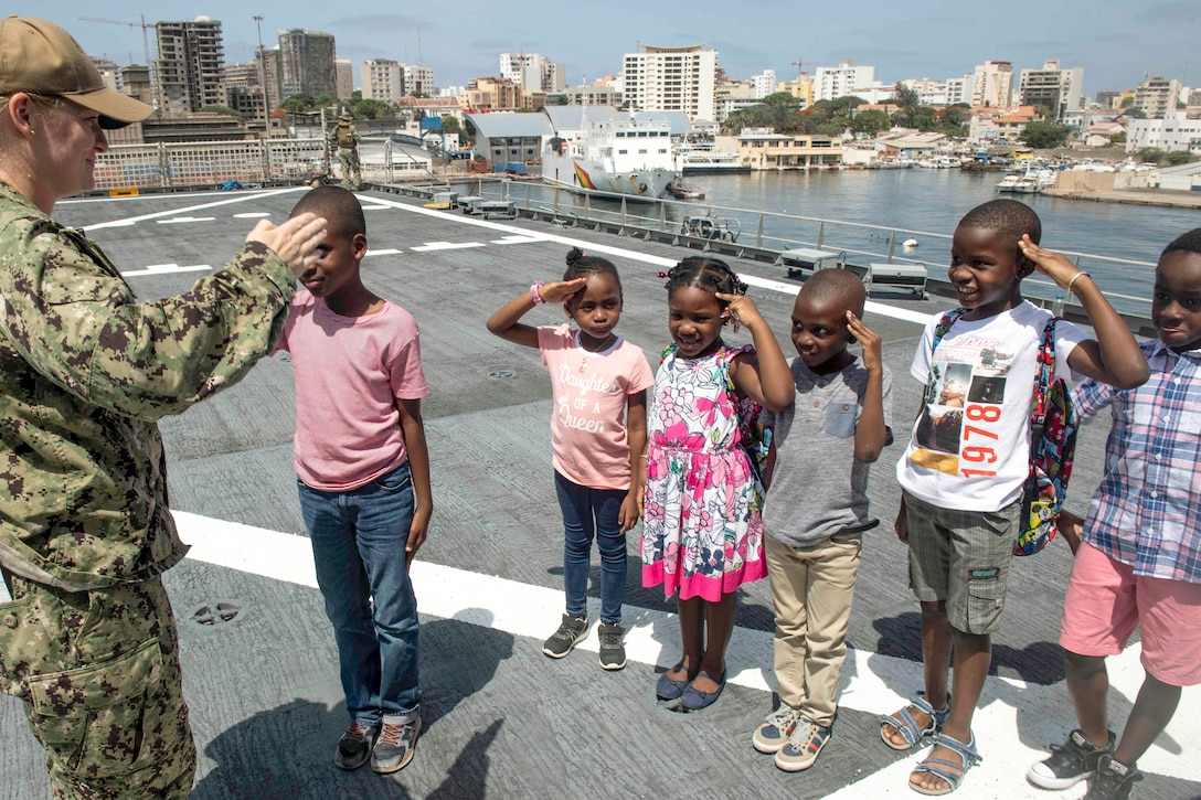 Kids show a sailor their practice salutes on a ship's deck.