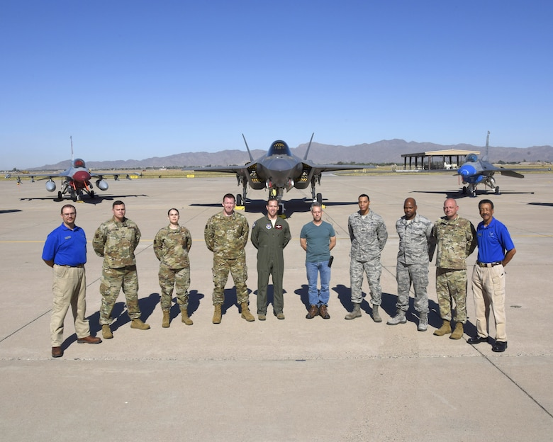 Members of the 56th Fighter Wing Safety Office stand for a group photo on the runway with a F-35A Lightning II and a F-16 Fighting Falcon, May 30, 2019, at Luke Air Force Base, Ariz. The Safety Office is comprised of three different sections; weapons, flight and occupational, these sections work together to ensure the safety of the Airmen and the base. (U.S. Air Force photo by Airman Brooke Moeder)