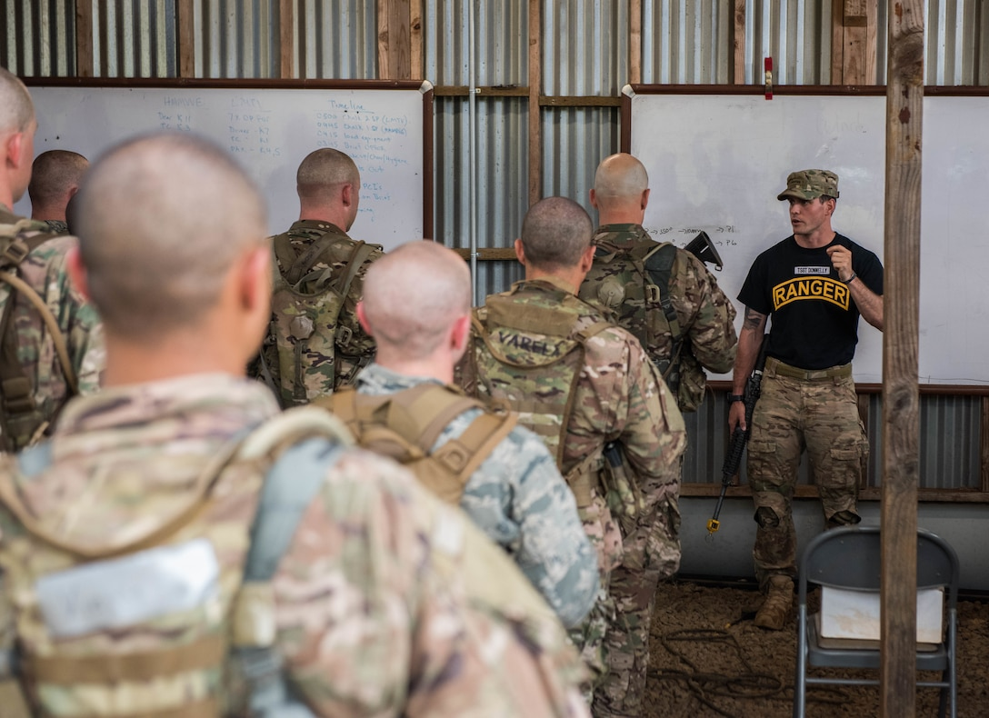 Tech. Sgt. Keegan Donnelly, Ranger Assessment Course lead cadre, talks to Airmen about land navigation during the Ranger Assessment Course, near Schofield Barracks, Oahu, Hawaii, May 13, 2019. Twenty-three Airmen from across the Air Force recently converged on a training camp for a three-week RAC near Schofield Barracks, May 12-31, 2019. For this iteration, the Air Force collaborated with the Army's 25th Infantry Division, Small Unit Ranger Tactics Program – their version of a pre-Ranger course – in order to gain a better understanding for the way the Army prepares their candidates for Ranger School. (U.S. Air Force photo by Staff Sgt. Hailey Haux)