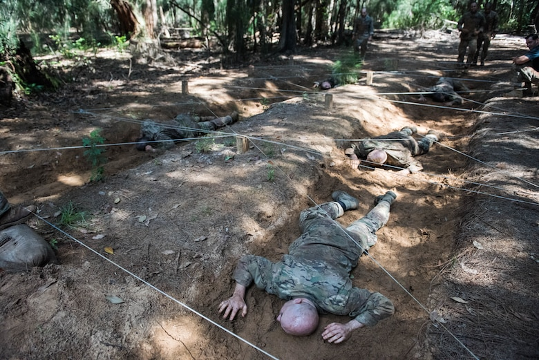 Ranger Assessment Course students low-crawl during the obstacle course for a Ranger Assessment Course near Schofield Barracks, Oahu, Hawaii, May 20, 2019. Throughout the 19-day course, Airmen were tested on their ability to perform land navigation, ambush, react to contact and squad attacks. Along with those assessments, the students went on runs and marches of different distances – all leading up to a 12-mile ruck march two days before graduation. (U.S. Air Force photo by Staff Sgt. Hailey Haux)