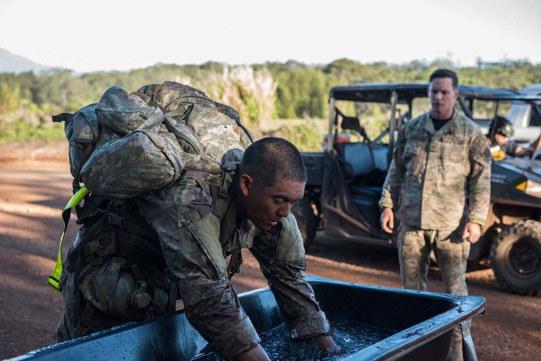 1st Lt. Jeffrey Poekhan, Ranger Assessment Course student, places his arms in ice water during a 12-mile ruck march near Schofield Barracks, Oahu, Hawaii, May 29, 2019. The purpose of the 19-day course is to prepare, assess and evaluate Air Force candidates for Army Ranger School. Of the 23 Airmen who began the Ranger Assessment Course, three dropped for personal motivational reasons and one dropped for medical reasons, leaving 19 standing at the end. Out of the 19, 11 Airmen met all the standards needed for a recommendation to go forward to Ranger School. (U.S. Air Force photo by Staff Sgt. Hailey Haux)
