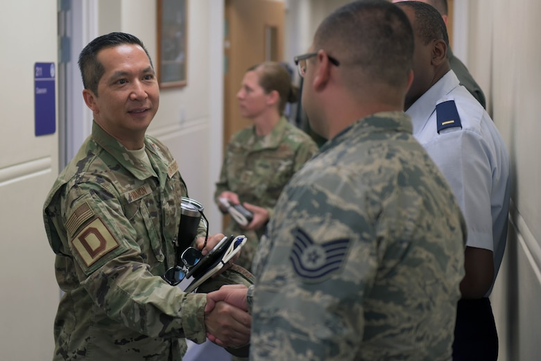 U.S. Air Force Col. Troy Pananon, 100th Air Refueling Wing commander, shakes hands with a 100th ARW Airman at RAF Mildenhall, England, July 9, 2019. Pananon began his military career in the United States Marine Corps, after leaving the USMC he completed his education and earned his commission in the Air Force. (U.S. Air Force photo by Senior Airman Benjamin Cooper)