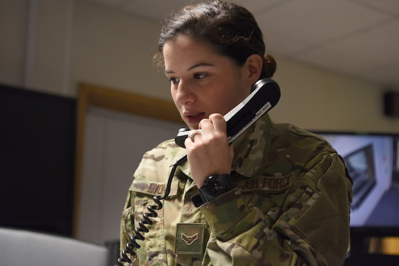 U.S. Air Force Airman 1st Class Kalie Lyons, 100th Air Refueling Wing Command Post emergency action controller, discusses flight plans with a KC-135 flight crew in the command post at RAF Mildenhall, England, Nov. 27, 2018. The command post Airmen are responsible for relaying classified and unclassified messages to the 100th ARW, 501st Command Support Wing and 352nd Special Operations Wing commanders and other base leadership. (U.S. Air Force photo by Airman 1st Class Brandon Esau)