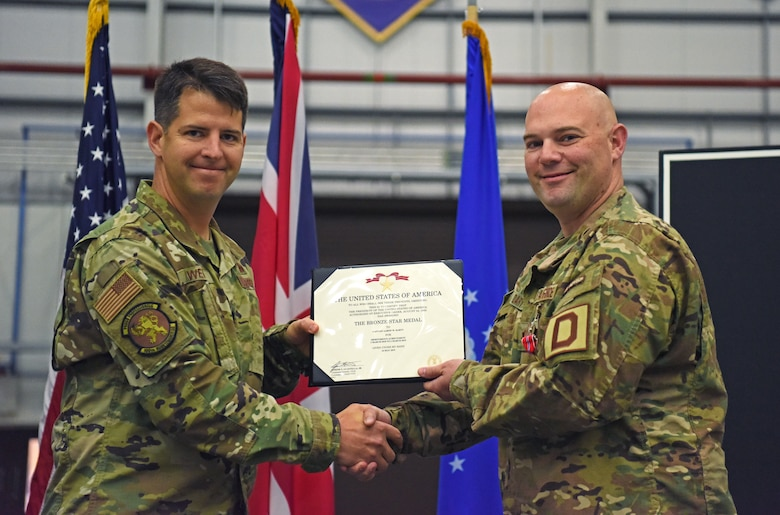 U.S. Air Force Lt. Col. Paul Weme, 100th Maintenance Group commander, presents Maj. Aaron Darty, 100th Maintenance Squadron operations officer, with a Bronze Star Medal during a ceremony held at RAF Mildenhall, England, July 1, 2019. Darty was recently awarded the Bronze Star Medal for meritorious achievement as operations officer and maintenance advisor in support of Operation Freedom Sentinel while deployed to Kandahar Airfield, Afghanistan. (U.S. Air Force photo by Airman 1st Class Brandon Esau)