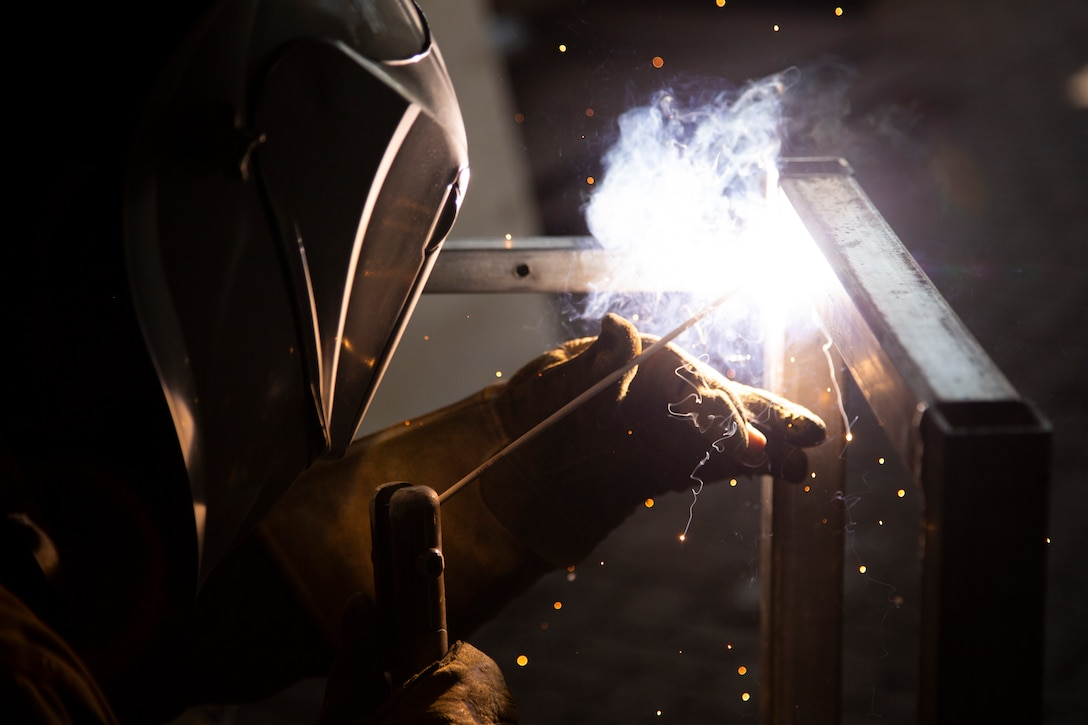 U.S. Marine Corps Cpl. Brandon Martin, a metal fabricator with the Logistics Combat Element, Marine Rotational Force – Darwin, uses a welding tool to assemble a steel frame at Robertson Barracks, Darwin, Australia, July 10, 2019. The LCE provides a unique skillset that allows the MRF-D Marine Air-Ground Task Force to be self-sustaining.