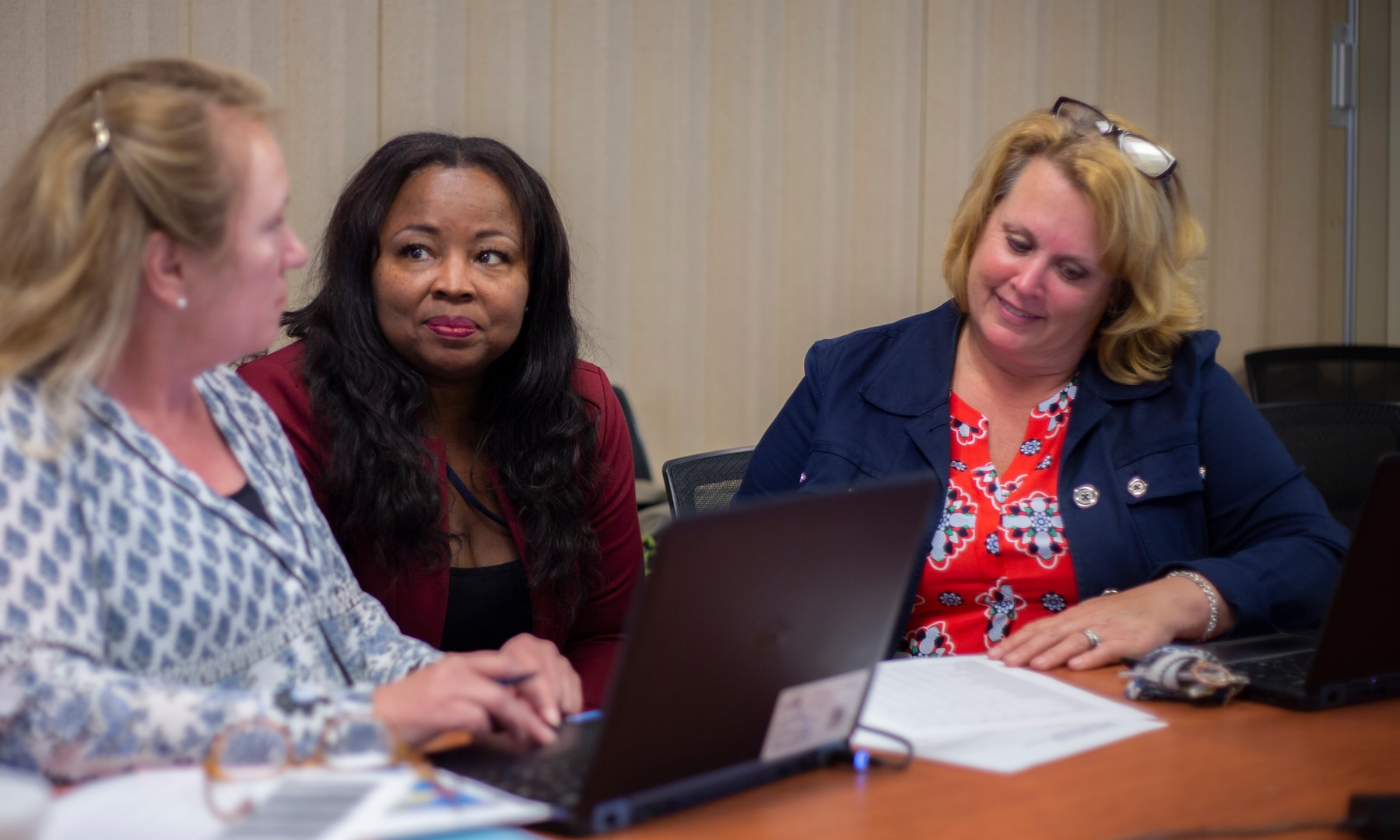 Three women discuss work items.