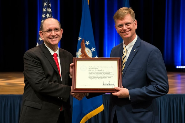 Acting Secretary of the Air Force Matthew P. Donovan presents the Presidential Rank Award to Dr. Glenn E. Sjoden, Chief Scientist for the Air Force Technical Applications Center during a ceremony at Pentagon in Washington, D.C., June 14, 2019. (U.S. Air Force Photo by Adrian Cadiz)