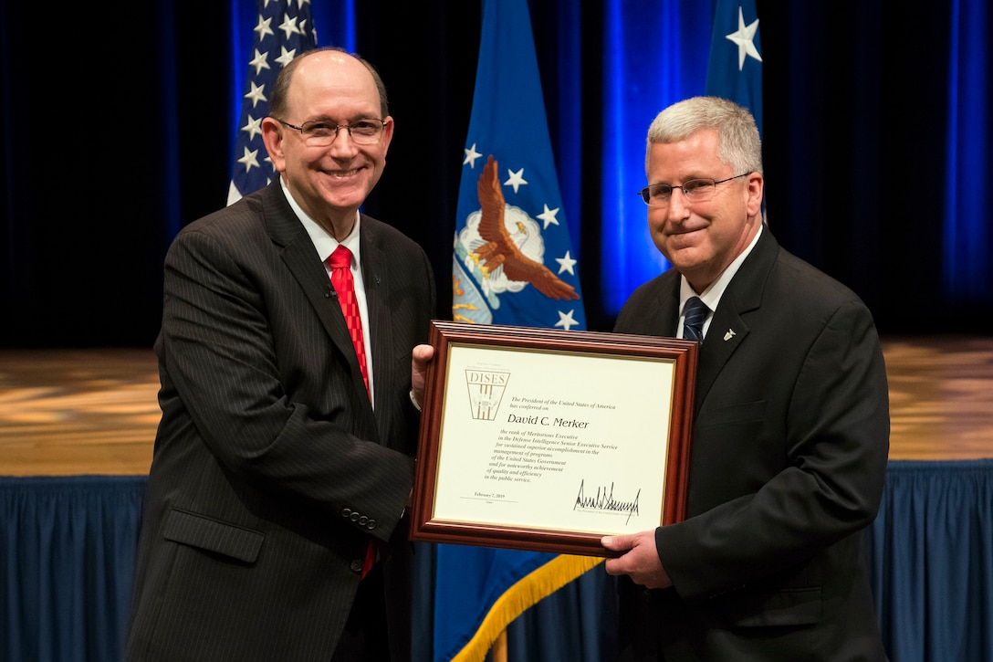 Acting Secretary of the Air Force Matthew P. Donovan presents the Presidential Rank Award to David C. Merker, Director of Systems Development for the Air Force Technical Applications Center during a ceremony at Pentagon in Washington, D.C., June 14, 2019. (U.S. Air Force Photo by Adrian Cadiz)