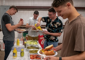 Members of the 97th Training Squadron get condiments from a buffet line during the quarterly Committee of 100 dinner, July 8, 2019, at Altus, Okla. The Committee of 100 is a quarterly event hosted by the community of Altus to welcome newcomers, returning deployers and family members to Altus AFB.
