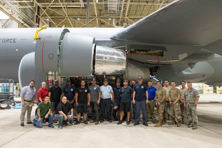 Maintainers pose for a photo after removing the first KC-46A engine.