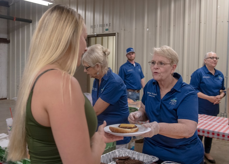 A student from the 97th Training Squadron receives food during the quarterly Committee of 100 dinner, July 8, 2019, at Altus, Okla. The Committee of 100 hosts the dinner celebration offering free food and a welcoming ceremony with games afterwards.