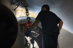 A maintainer helps remove a KC-46A engine.