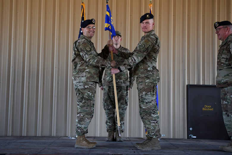 U.S. Air Force Maj. Shawn Chamberlin, left, accepts the guidon and command of the 377th Weapon System Security Squadron from Col. Theodore Breuker, 377th Security Forces Group commander, during a change of command ceremony at Kirtland Air Force Base, N.M., July 9, 2019. Chamberlin previously commanded the 377th Security Forces Squadron. (U.S. Air Force photo by Senior Airman Eli Chevalier)