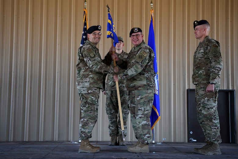 U.S. Air Force Lt. Col. Joseph Parsons, right, outgoing 377th Weapon System Security Squadron commander, passes the guidon to Col. Theodore Breuker, 377th Security Forces Group commander, during a change of command ceremony at Kirtland Air Force Base, N.M., July 9, 2019. Parsons is scheduled to retire from active duty on July 10, 2019. (U.S. Air Force photo by Senior Airman Eli Chevalier)
