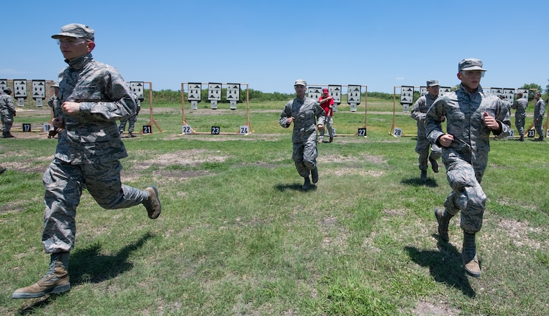 Air Force Basic Military Training trainees run back to their firing position after seeing their targets during a weapons familiarization course June 8 at Joint Base San Antonio-Medina Annex. The firing range allows instructors to train 244 BMT trainees daily, four days a week, qualifying more than 40,000 BMT trainees in the M-4 carbine annually.