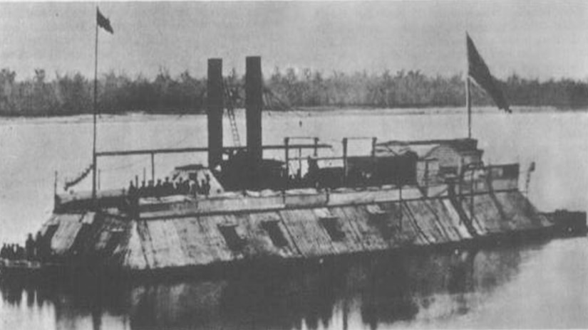 A ship covered in iron with two flags, two smokestacks and several sailors standing on it sails down a river.