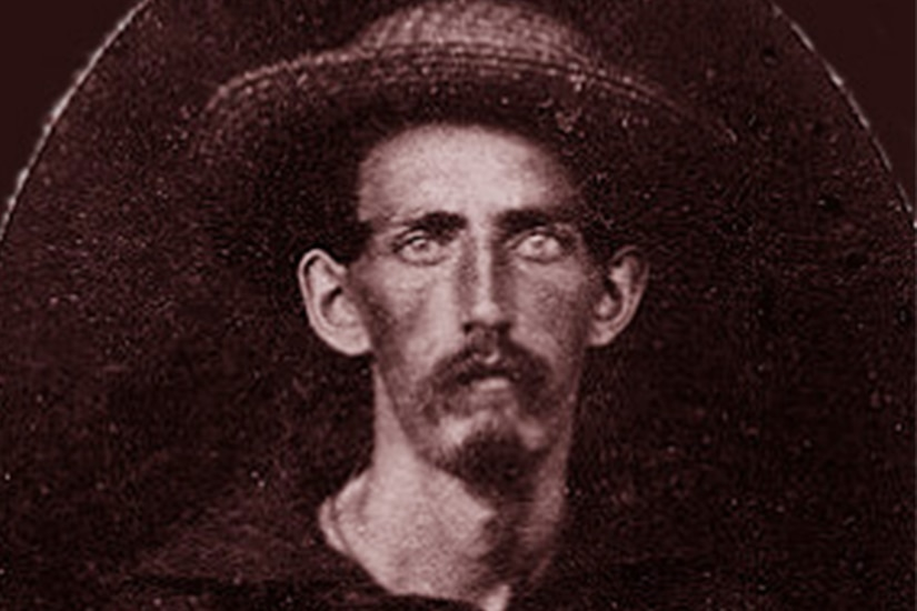 A man with a mustache wearing a wide-brimmed hat and Navy shirt looks at the camera.