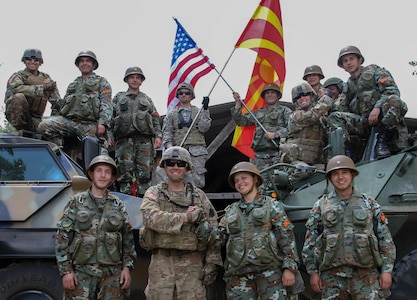 American Soldiers from the 56th Stryker Brigade Combat Team, Pennsylvania Army National Guard, and soldiers from the Republic of North Macedonia by their tactical vehicles to show unity between the two nations, following the Exercise Decisive Strike's opening ceremony at the Training Support Centre Krivolak , North Macedonia, June 5, 2019.