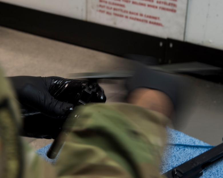 Staff Sgt. Rossitor Alexander, an instructor assigned to the 628th Security Forces Squadron Combat Arms Training and Maintenance flight, brushes carbon residue off of an M9 pistol after firing it at Joint Base Charleston, S.C. July 1, 2019. CATM facilitates readiness by equipping Airmen with the knowledge and skills to use weapons properly, and provides support to local and regional military branches. CATM instructors qualify for the weapons annually to maintain proficiency.