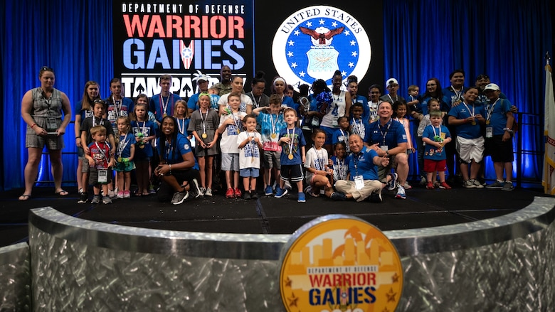 Children of Team Air Force athletes join U.S. Army Brig. Gen. Brian Cashman following a ceremony where the children received medals for their support at the Tampa Convention Center, June 27, 2019. The Warrior Games were established in 2010 as a way to enhance the recovery and rehabilitation of wounded, ill and injured service members and expose them to adaptive sports. Approximately 300 athletes are participating in 13 adaptive sport competitions June 21-30. The athletes represent the United States Army, Marine Corps, Navy, Air Force and Special Operations Command. Athletes from the United Kingdom, Australia, Canada, the Netherlands, and Denmark will also compete. (DoD photo by Staff Sgt. Vito T. Bryant)