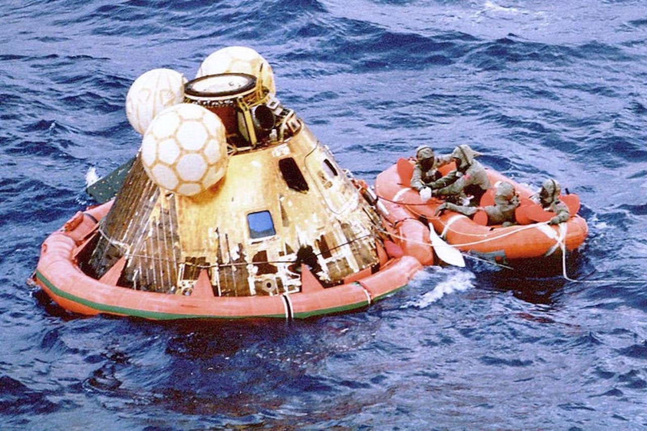 Divers ride ocean in raft next to space capsule
