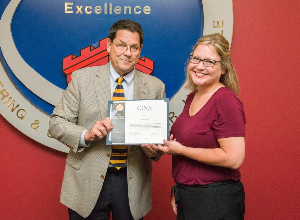 """Roy W. Malone Jr., the director of the Office of Center Operations at NASA's Marshall Space Flight Center, presents the """"Capturing It Now Award"""" to Jaclyn Fuller, project manager in the Facility Reduction Program at the U.S. Army Engineering and Support Center, Huntsville, June 17, 2019. Malone visited Huntsville Center to personally recognize Fuller for her work as project manager for the NASA Santa Susana Field Laboratory demolition project in southern California."""