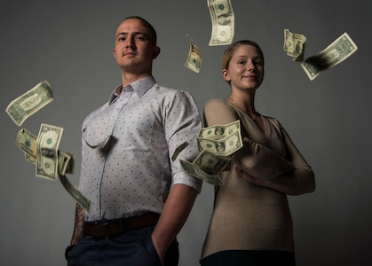 Senior Airman Clayton Wear and Airman 1st Class Hanah Abercrombie, 30th Space Wing Public Affairs photojournalists ,pose for a photo as money falls down April 3, 2019, at Vandenberg Air Force Base, Calif.