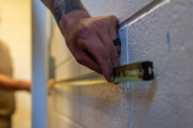 Airmen from the 23d Civil Engineer Squadron (CES) Water and Fuels Systems Maintenance shop measure a wall, July 2, 2019, at Moody Air Force Base, Ga. Airmen from the 23d CES Water and Fuels Systems Maintenance are on-call 24/7 to sustain and maintain the base, water, sewer and gas lines and upkeep of the 696 facilities with water and fuel infrastructure. (U.S. Air Force photo by Airman 1st Class Taryn Butler)