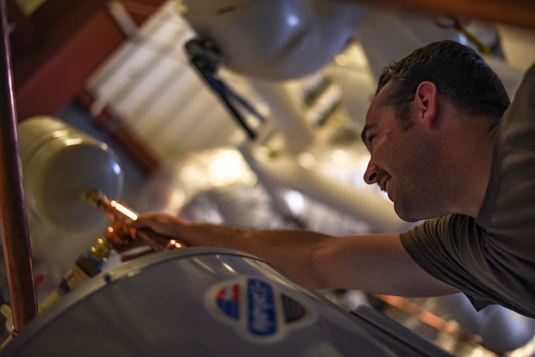 Staff Sgt. Daniel Champion, 23d Civil Engineer Squadron (CES) water and fuel systems maintenance craftsman, places an expansion tank, on a water heater, July 2, 2019, at Moody Air Force Base, Ga. Airmen from the 23d CES Water and Fuels Systems Maintenance are on-call 24/7 to sustain and maintain the base, water, sewer and gas lines and upkeep of the 696 facilities with water and fuel infrastructure. (U.S. Air Force photo by Airman 1st Class Taryn Butler)