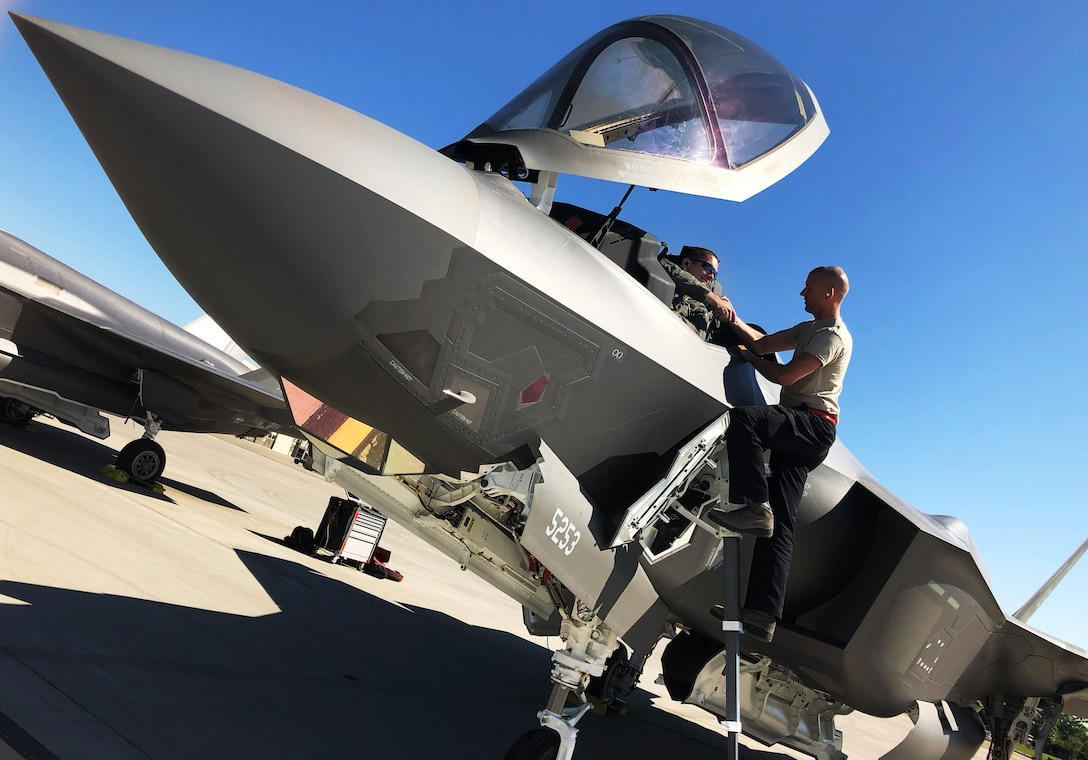 An F-35A maintainer hands Lt. Col. Christopher White his gear as he prepares for an engine check prior to the first sortie of the day July 11.The 388th Fighter Wing's 34th Fighter Squadron is operating out of Mountain Home AFB, Idaho, while Hill AFB's runway is under construction. (U.S. Air Force photo by Micah Garbarino)