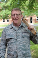 Master Sgt. Tony Loving, 932nd Force Support Squadron personnel systems, poses for a photo with his guitar, July 10, 2019, Scott Air Force Base, Illinois. He has witnessed many unit changes, as well as being involved in making music after work. Loving has helped on improvement within military processes during the day.  (U.S. Air Force photo by Lt. Col. Stan Paregien)