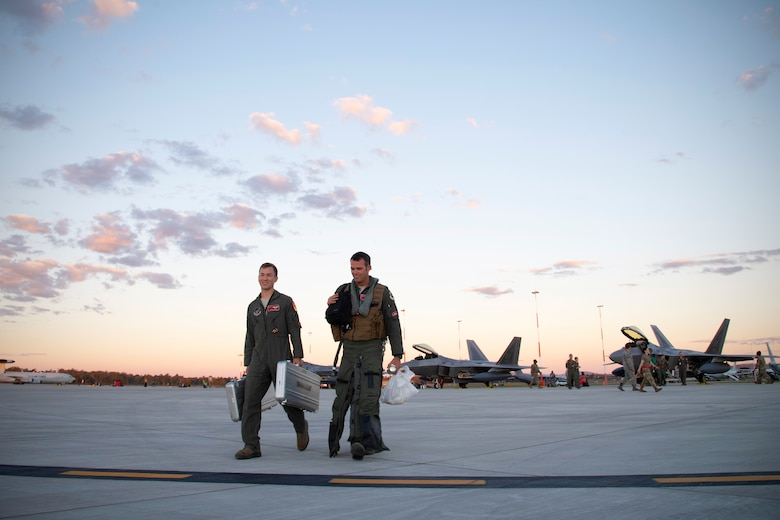 U.S. Air Force Lt. Col. Ryan Graf, 90th Fighter Squadron commander, right, and USAF Capt. Jonathan Weed, with the 90 FS, Joint Base Elmendorf-Richardson, Alaska, depart the flightline after arriving July 9, to Royal Australian Air Force Base Amberley, Australia, in support of Talisman Sabre 19. Talisman Sabre is a month-long exercise along the east coast of Australia that incorporates force members from Australia and the United States in amphibious landings, land force maneuver, urban operations, air operations, maritime operations and special forces activities. (U.S. Air Force photo by Senior Airman Elora J. Martinez)
