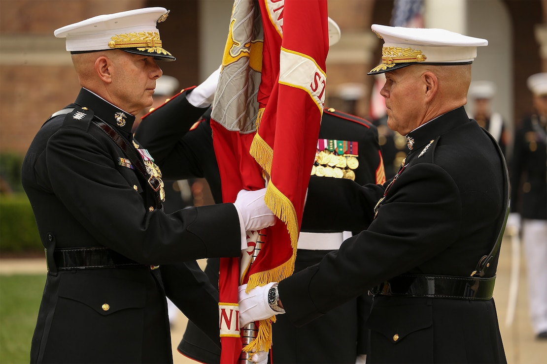 General Robert B. Neller, 37th Commandant of the Marine Corps, passes the Marine Corps Battle Color to Gen. David H. Berger, 38th Commandant of the Marine Corps during a passage of command ceremony at Marine Barracks Washington, D.C., July 11, 2019. General Neller relieved his duties as commandant of the Marine Corps to Gen. Berger.